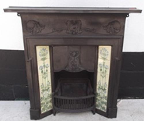 A decorative Art Nouveau cast iron tiled combination fireplace