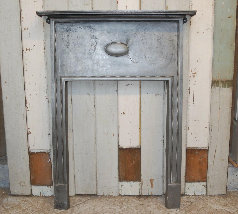 FS0055 AN ANTIQUE CAST IRON BURNISHED FIRE SURROUND C.1920'S