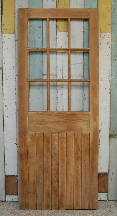 DI0673 AN INTERNAL RECLAIMED STRIPPED OAK DOOR WITH PANELS FOR GLAZING