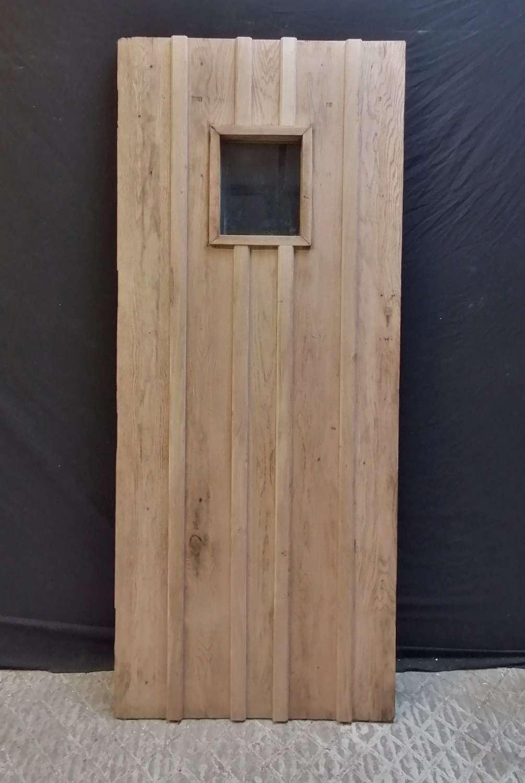 DE0895 A RECLAIMED OAK EXTERIOR DOOR WITH GLAZED PANEL